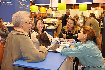 La présidente de Femmes au-delà des mers, Gisèle Bourquin, discute et rit avec d'autres femmes au salon du livre 2012.